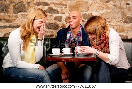 Three friends in cafe discussing and having fun