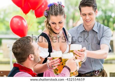 Three friends in Munich Beer garden clinking - stock photo