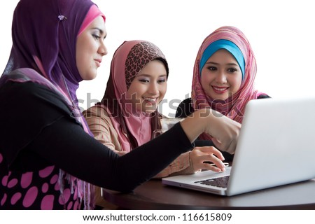three friends laughing at content on a laptop - stock photo