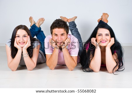 Three friends lying  down on laminate flooring in a row with legs up and holding hands on  faces - stock photo