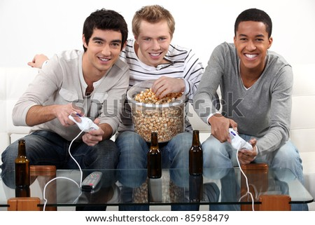 Three friends playing video games while drinking beer. - stock photo