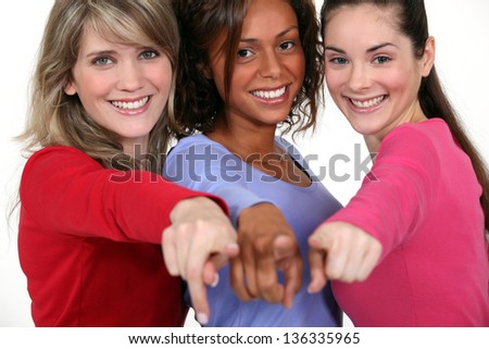 Three friends pointing at the camera. - stock photo