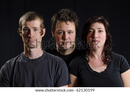 Three friends pose for a serious portrait