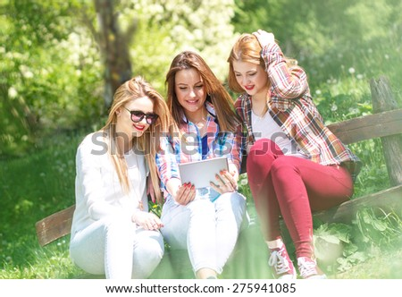 Three friends sitting in a park and looking something on tablet - stock photo