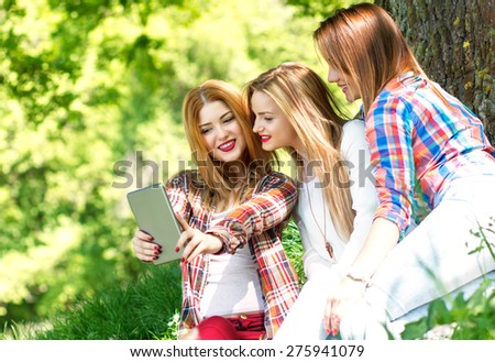 Three friends sitting in a park and making selfie with tablet - stock photo