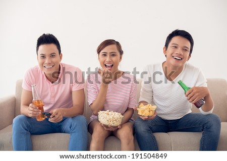 Three friends sitting on sofa and watching TV - stock photo