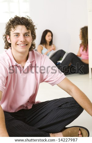 Three friends sitting on the floor. A girls talking with themselves. A boy smiling and looking at camera. Focused on a boy. - stock photo