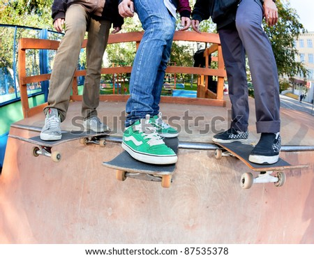 Three friends skateboarders in the skatepark rest after skating - stock photo