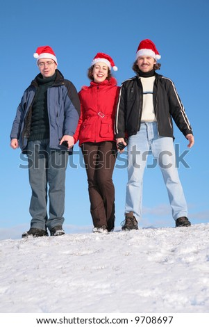 three friends stand on snow in santa claus hats