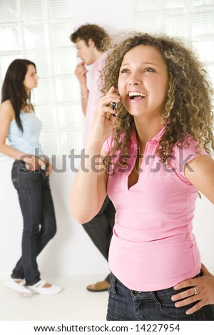 Three friends standing near window. A boy talking with girl in blue shirt. A girl in pink shirt smiling and talking by mobile phone. Focused on girl in pink shirt. - stock photo