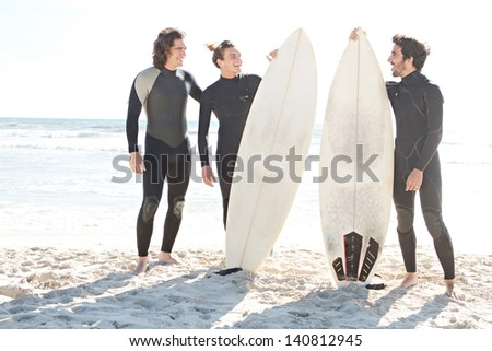 Three friends surfers men standing together on a white sand beach on a vacation trip, smiling and being joyful with their surfing boards against a sunny blue sky. - stock photo
