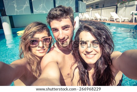 three friends taking selfie in the swimming pool. concept about friendship, people,technology,selfie, and fun - stock photo