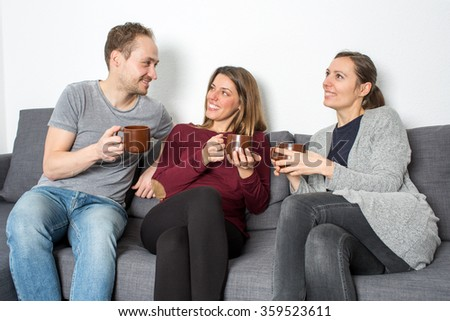 Three friends talking and drinking coffee - stock photo