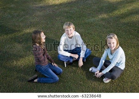 Three friends (10 to 11 years) sitting together on grass - stock photo