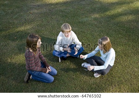 Three friends (10 to 11 years) sitting together on grass chatting