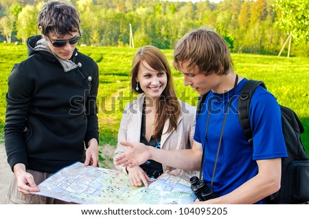 Three friends traveling, they look at a map - stock photo