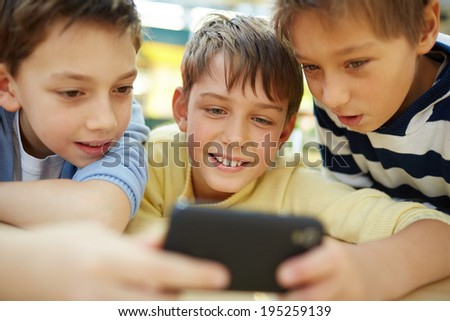 Three friends using a new smartphone - stock photo