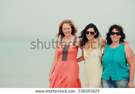 three friends walking on the beach - stock photo