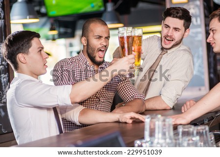 Three friends with beer. Three cheerful friend clink beer at the bar and drink a beer while the bartender is standing on the bar. Friends having fun together - stock photo