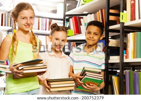 Three friends with books standing near bookshelf in the library - stock photo