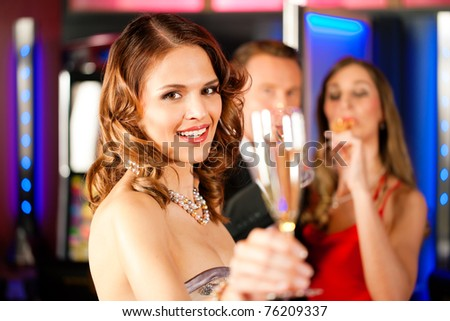 Three friends with champagne in a bar or casino