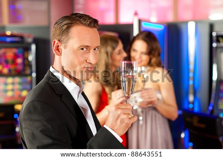 Three friends with champagne in a bar or casino, a man is looking in the camera - stock photo