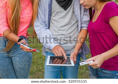 Three friends with electronic gadget in park. Close up.