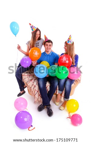 Three friends with hats and balloons sitting on the couch isolated - stock photo