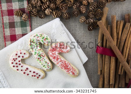 Three frosted and decorated candy cane shaped sugar cookies on a cloth napkin with cinnamon sticks and pine cones - stock photo
