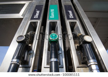 Three fuel nozzles at a gas station - stock photo