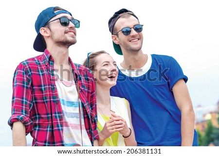 Three Fun and successful guys in sunglasses go ahead. Young friends have fun together on the street and smile at each other. - stock photo
