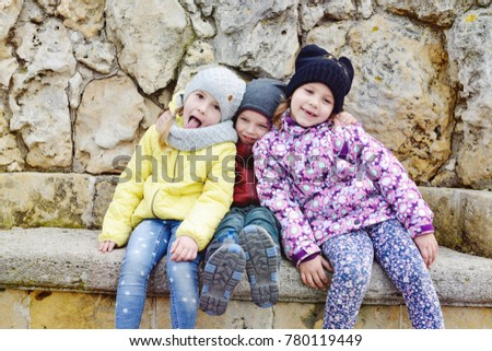three funny children outdoors in cold time