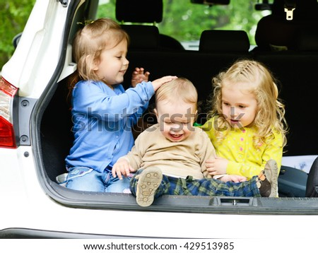 three funny children sitting in the car, focus on the boy - stock photo