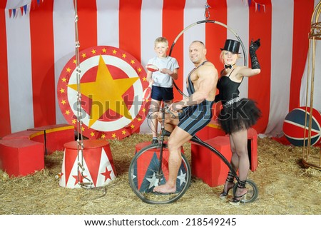 Three funny circus strong man, woman in cylinder and boy on retro bike with balloons in striped tent - stock photo