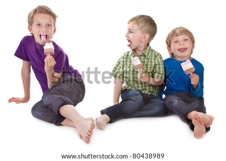 three funny kids eating ice lolly on white background - stock photo