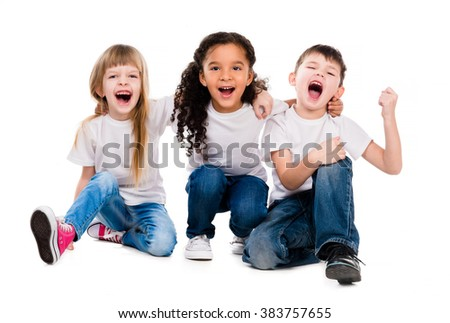 three funny trendy children laugh sitting on the floor - stock photo