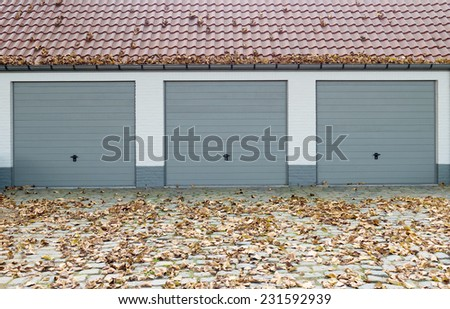 Three garage doors during fall season - stock photo