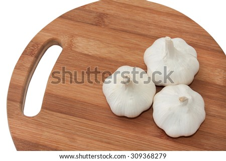 Three garlics on the kitchen wooden board. - stock photo