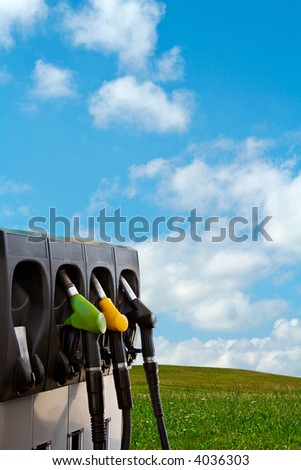 Three gas pump nozzles over a nature background