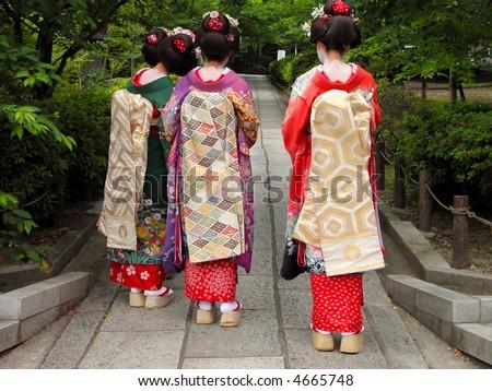 Three geisha wearing kimonos in a traditional street of Kyoto,Japan - stock photo