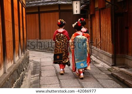 Three geishas walking on a street of Gion (Kyoto, Japan) - stock photo