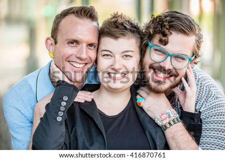 Three gender fluid friends pose and smile - stock photo
