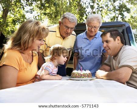 Three generation Caucasian family seated at picnic table celebrating female child's birthday with cake. - stock photo