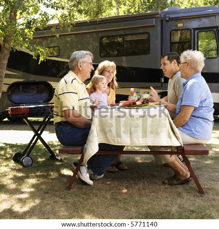 Three generation Caucasian family seated at picnic table in front of recreational vehicle talking. - stock photo