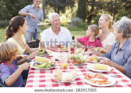 Three Generation Family Enjoying Barbeque In Garden Together - stock photo