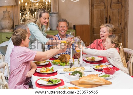 Three generation family enjoying christmas dinner together at home in the living room