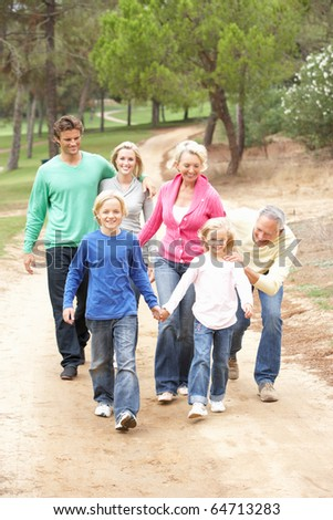 Three Generation Family enjoying walk in park - stock photo