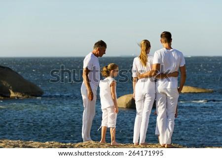 Three generation family having a walk on a rocky coast. Rear view. - stock photo