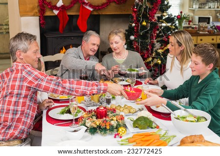 Three generation family having christmas dinner together at home in the living room - stock photo