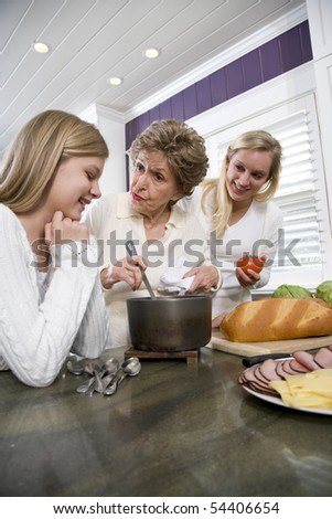 Three generation family in kitchen serving lunch - stock photo